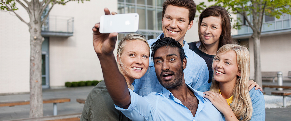 A group of students take a selfie in front of the main entrance