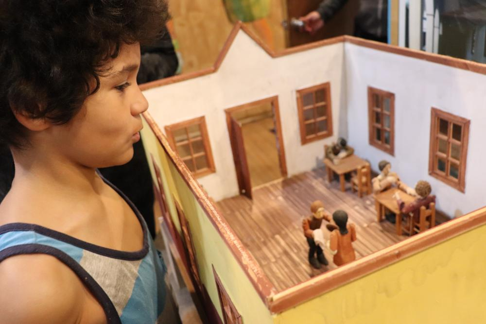 A boy looking at a model of a house. Photo.