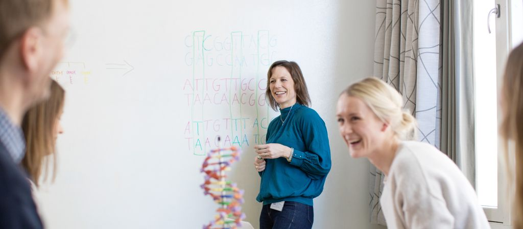 Scientists smiling in front of a white board with notes