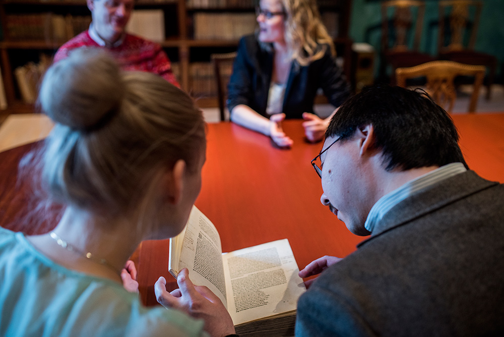 Researchers studying and discussing old books. Photo.
