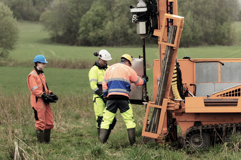 Photo. Geotechnical Engineers in field lab using drilling rig.