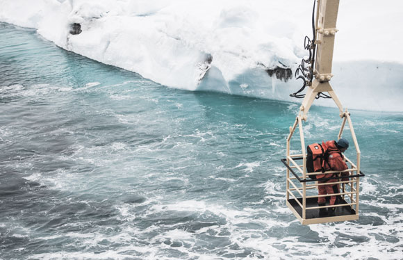 Photo. Researchers beeing transportet to an iceberg by a crane.