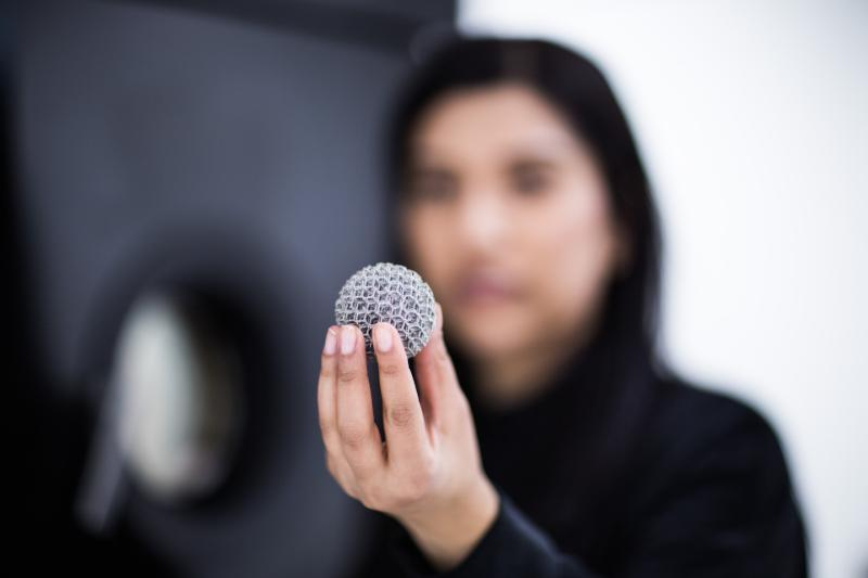 Student holding 3D metal printed object