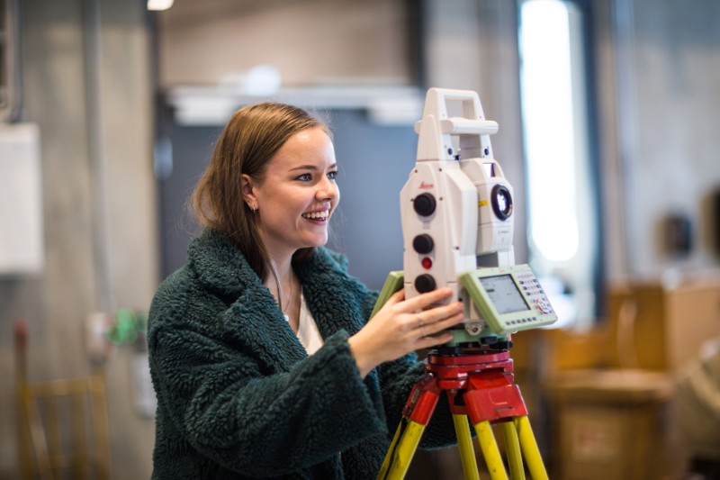 Picture of student with land surveing equipment