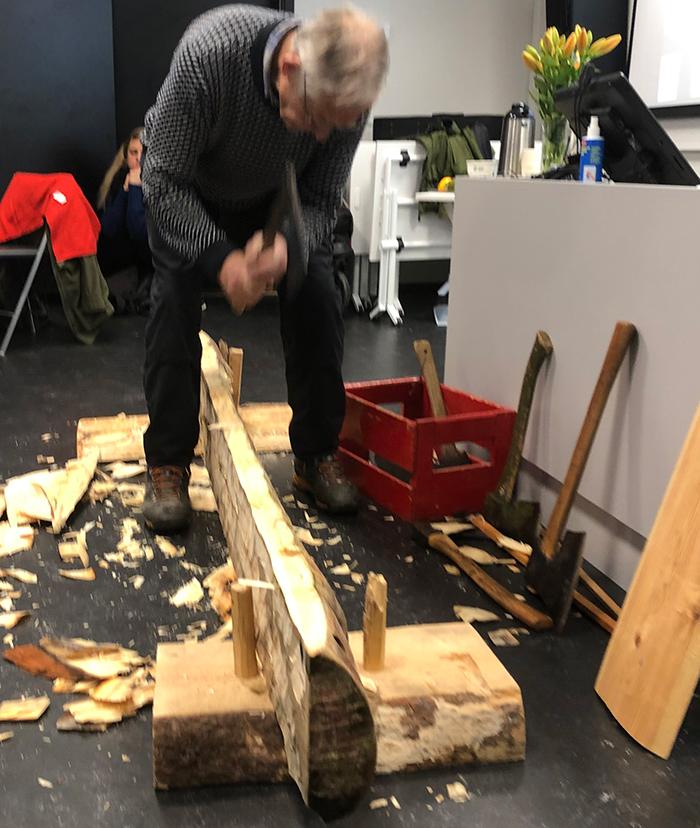 Jon Godal jobber med et stort stykke trearbeid i et klasserom. Mange fliser på gulvet. Photo