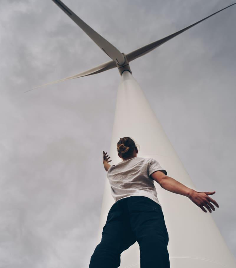 Man reaching towards windmill, photo