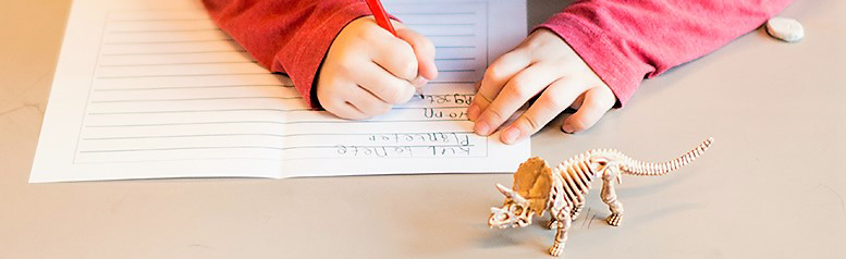 Boy writing with pencil. Foto