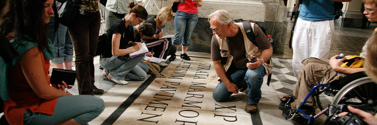 Atudents and teacher studying letters on a floor in Rome.