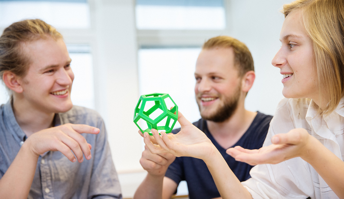 Students admiring a 3d-printed dodecahedron. Photo.