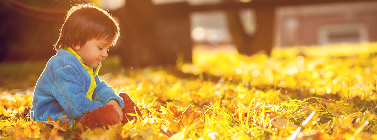 A boy sitting in the grass. Photo.