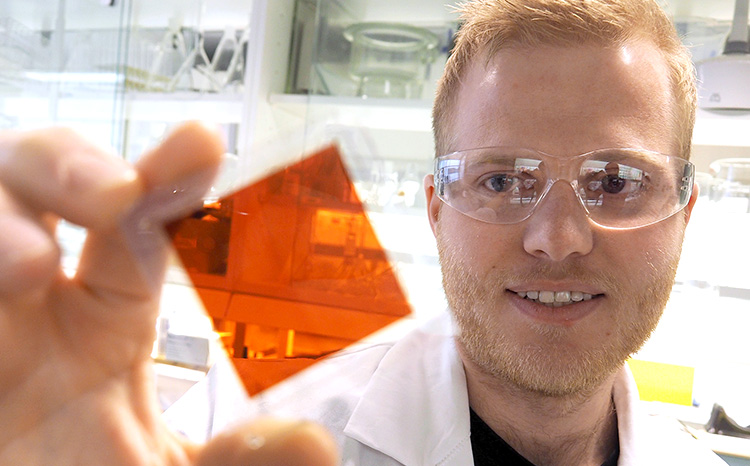 PhD candidate holding up a solar cell. Photo