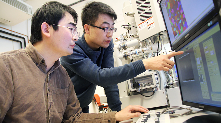 Postdoc Kai Zhang and PhD candidate Hailong Jia are investigating the extrusion microstructure by electron back-scattered diffraction (EBSD). Photo: Per Henning/NTNU