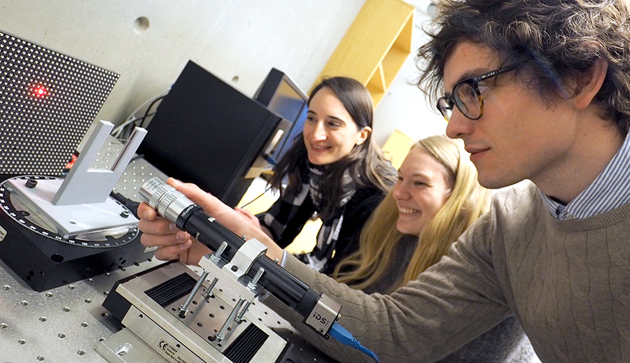Three students in the physics lab doing an experiment with a red laser beam. Photo