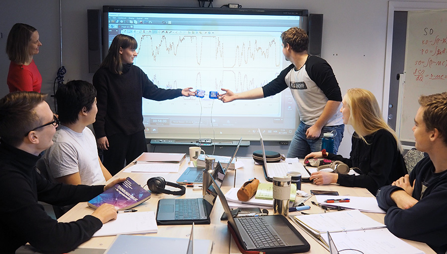 Two students demonstrating a concept in physics with teacher in front of other students. Photo