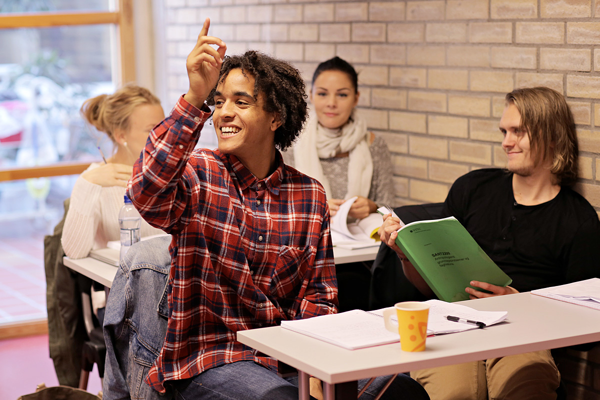Student raising his hand in class, other students sitting behind him. Photo.