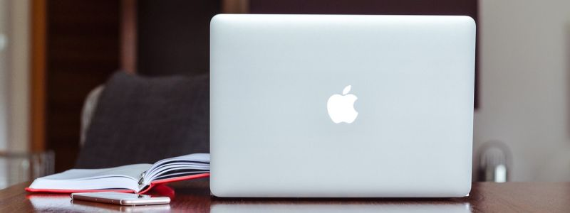 photo of a Mac and some books