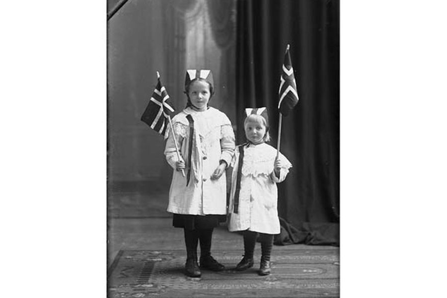 Two little girls in white dresses, Norwegian flags