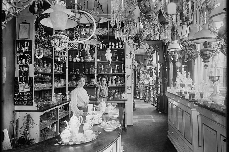 Interior and employees in a shop selling products of glass and china, lamps and mirrors, 1902