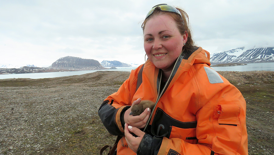 Emily Hill holding a baby bird in the arctic. Photo