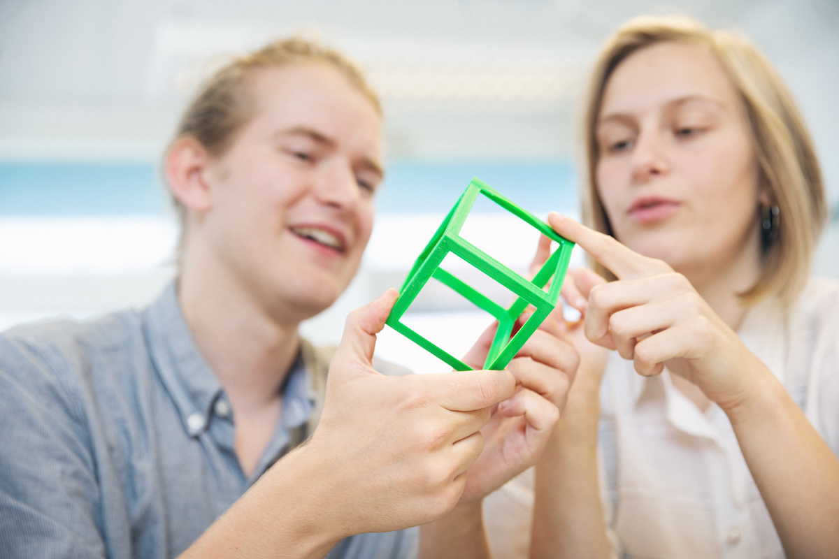 Two students studies a green cube. Photo.