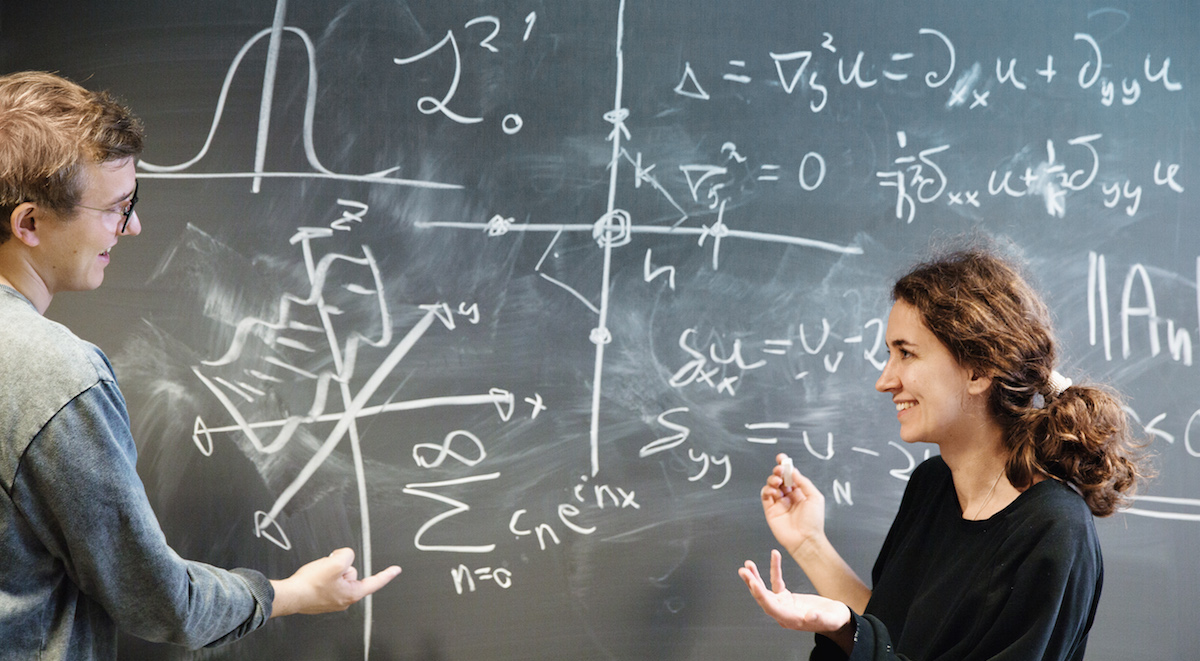Mathematics students working at the blackboard. Photo