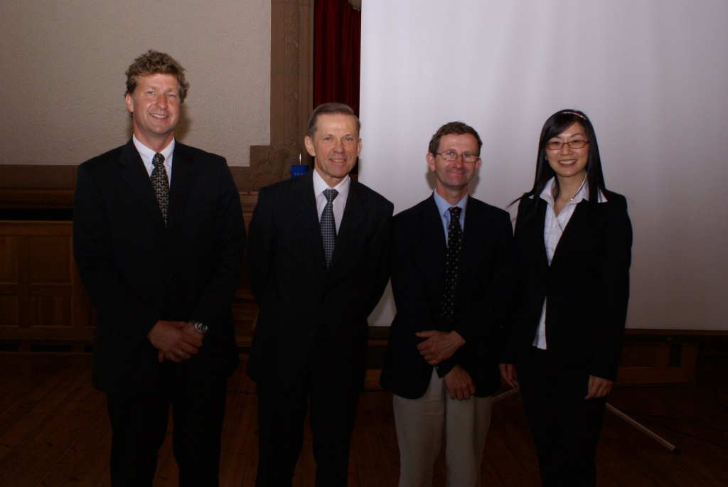 Professors and student standing in front of a projector screen. Photo.