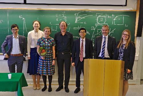Professors and students standing in front of a blackboard. Photo